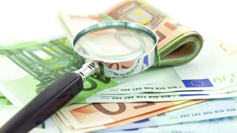 валюта и увеличительное стекло